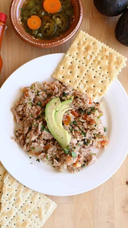 Atun a la Mexicana served with saltine crackers on a white plate and topped with sliced avocado.