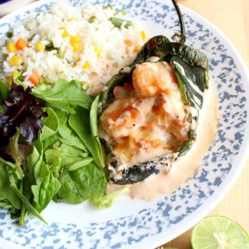 A shrimp chile relleno served on a plate next to a salad and rice.