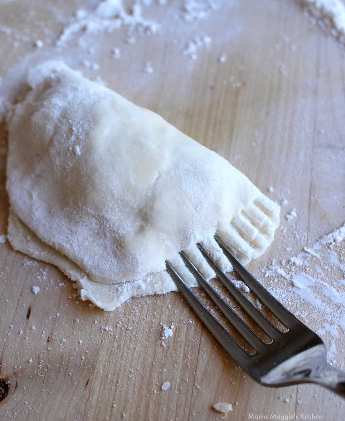 A fork sealing the edge of an empanada.