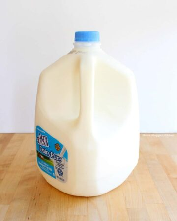 A gallon of milk on a wooden table.