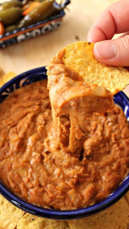 A hand holding a chip with frijoles puercos over a blue bowl.