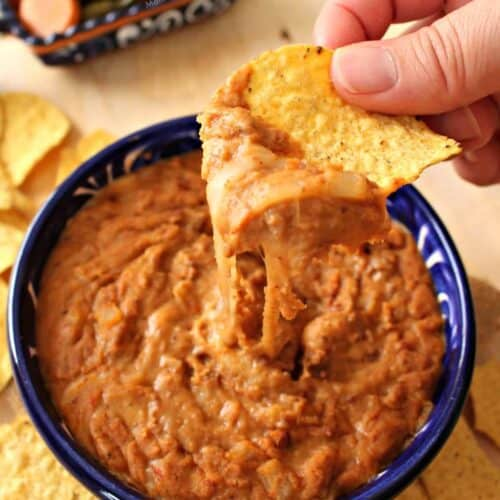 """A hand holding a chip of liberoles puercos over a blue bowl. """"Srcset ="""" """"srcset ="""" https://inmamamgieskitchen.com/wp-content/uploads/2020/04/Frijoles-Puercos-500x500.jpg 500w, https://inmamamaggieskitchen.com/wp-content/uploads/2020 /04/Frijoles-Puercos-150x150.jpg 150w, https://inmamaggieskitchen.com/wp-content/uploads/2020/04/Frijoles-Puercos-100x100.jpg 100 w """"sizes ="""" (max width: 200 px 100 vw, 200 px"""
