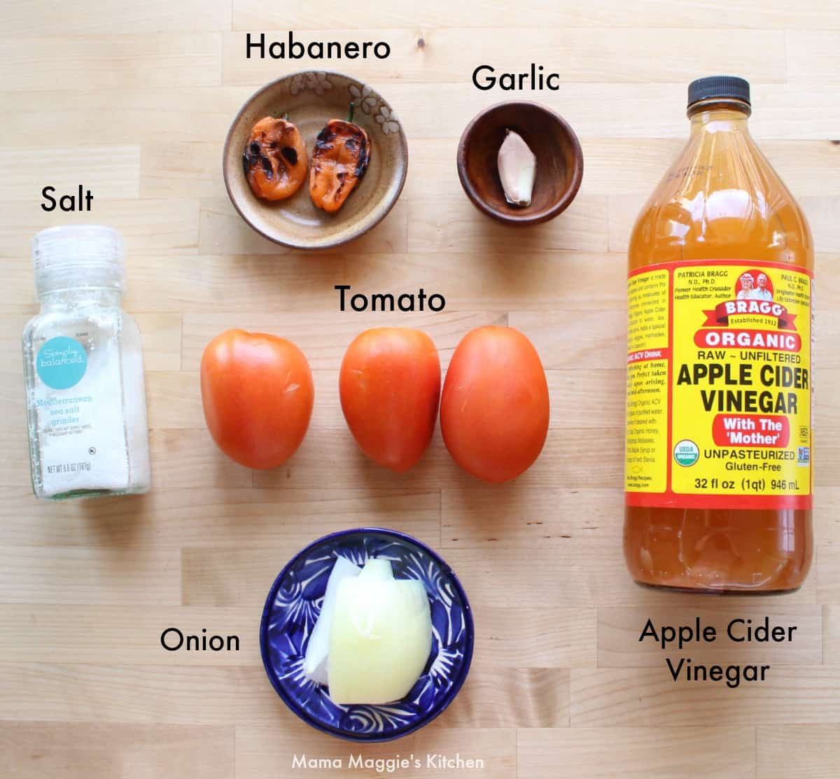 The ingredients for Tomato Habanero Salsa on a wooden surface.