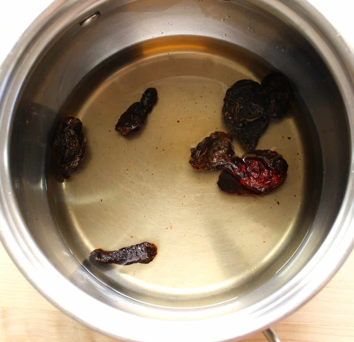 Dried morita chiles covered with water in a stock pot.