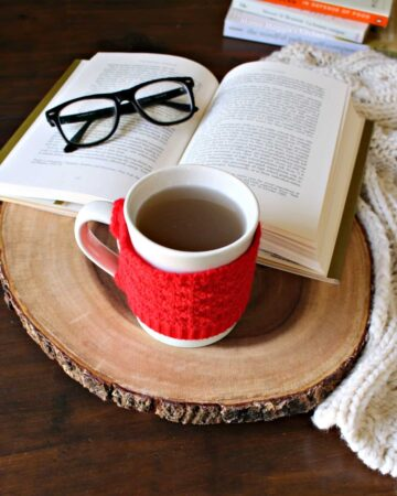 A cup of oregano tea on a wooden surface next to a book and glasses.