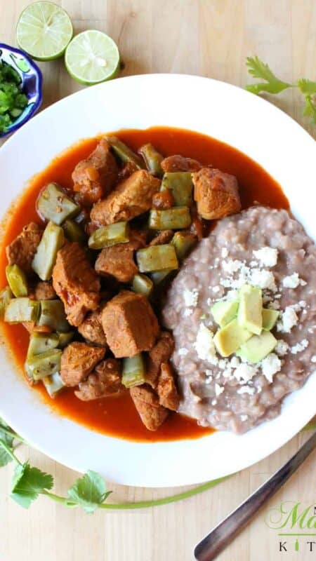 Pork and nopales in chile colorado served on a white plate with fried beans.