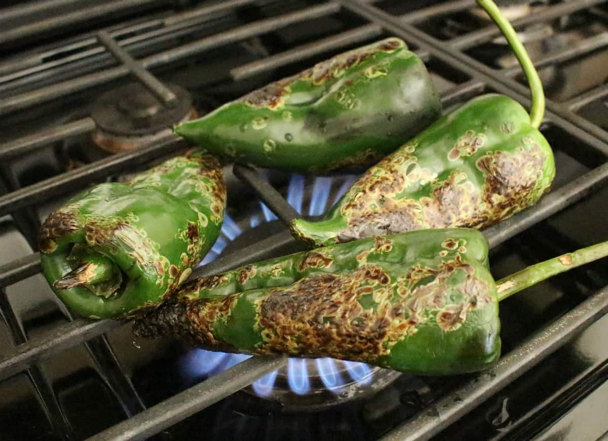 Poblano peppers roasting on a gas stove.