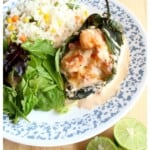Shrimp Chile Relleno served on a plate next to a salad and rice.