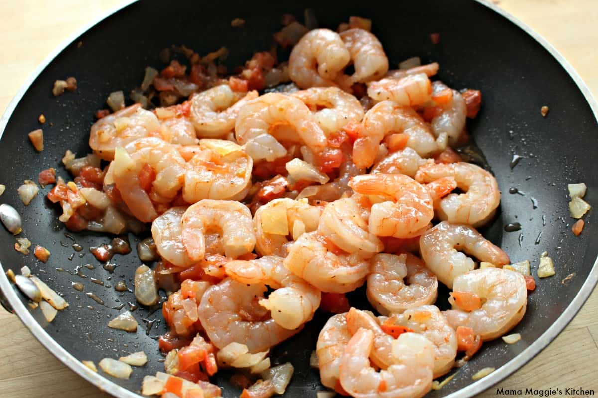 A skillet cooking shrimp and tomato.