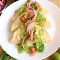 Potato Tacos Dorados on a white plate topped with lettuce, tomatoes, and pickled red onions.