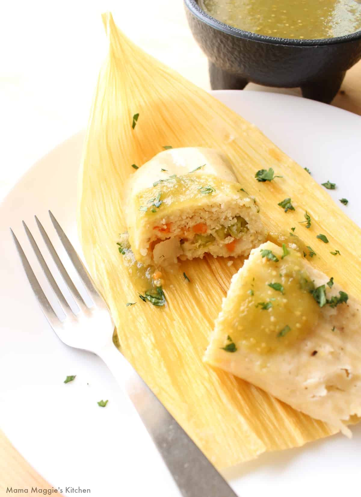 A vegetable tamal cut in half topped with salsa verde and chopped cilantro.