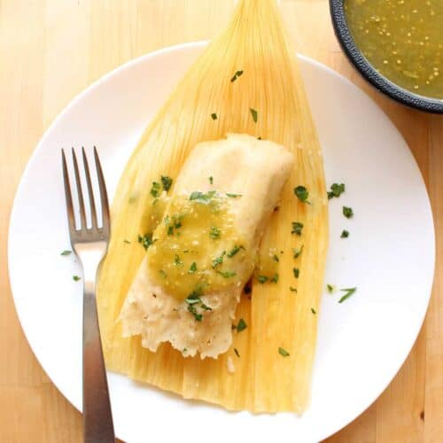 A vegetable tamal on top of a corn husk drizzled with green salsa verde and chopped cilantro.
