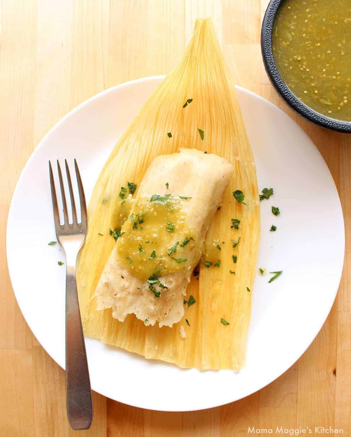 A tamal on top of a corn husk drizzled with green salsa verde and chopped cilantro.