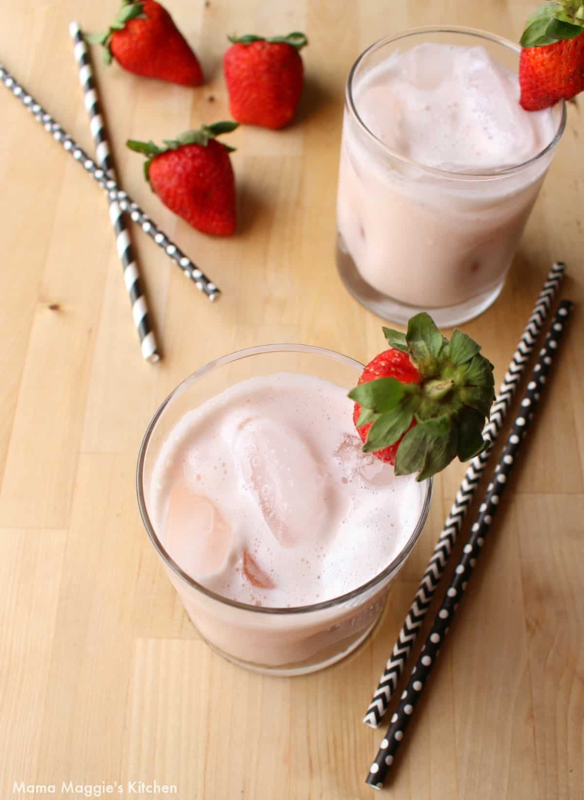 Two glasses filled with Agua de Fresa and topped with whole strawberries surrounded by straws.