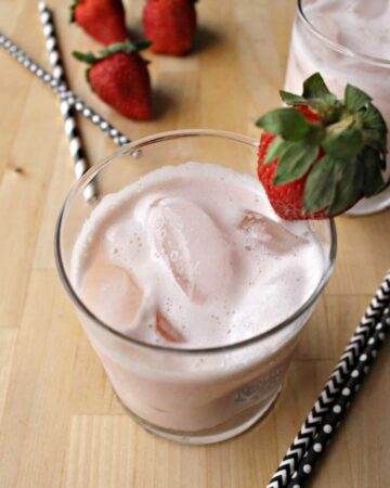 A glass of Agua de Fresa topped with a whole strawberry next to straws.