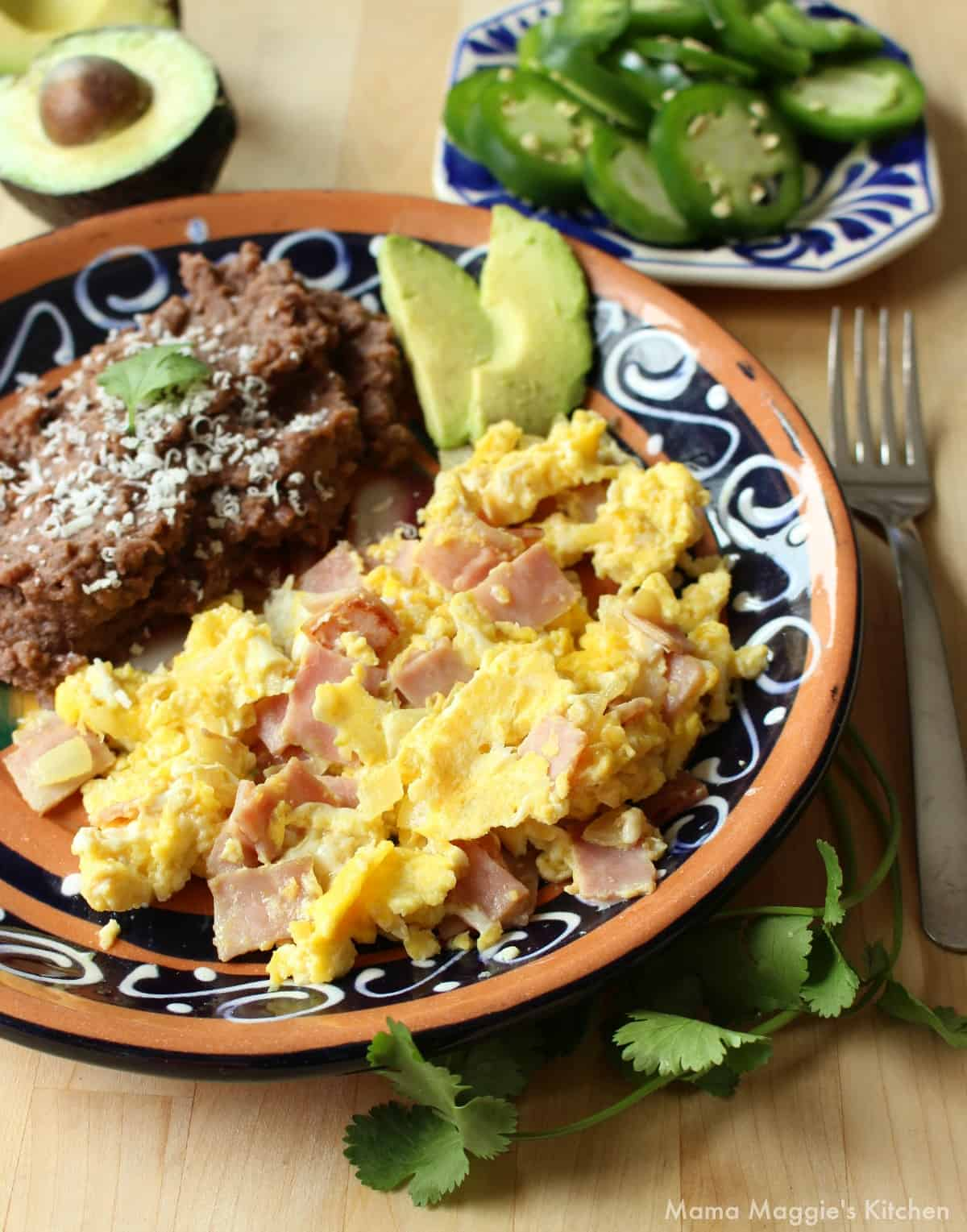 Huevos con Jamon served on a plate next to refried beans and avocado slices.