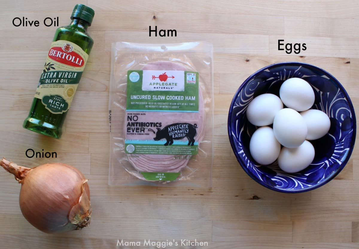 Ingredients for Huevos con Jamon on a wooden surface.