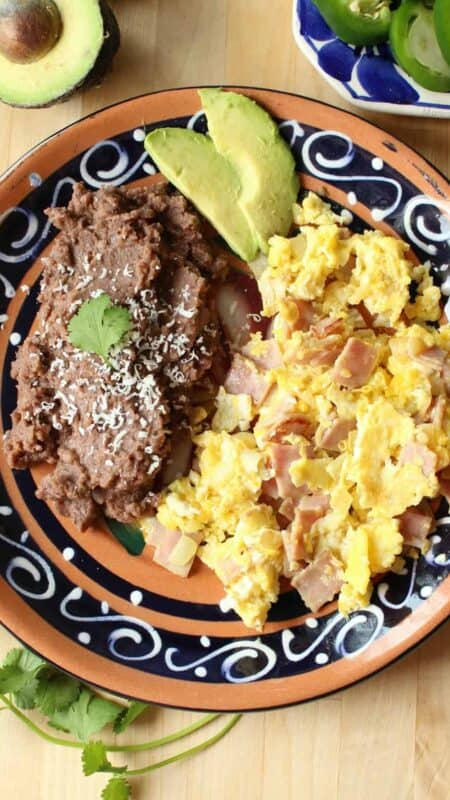 Huevos con Jamon served on a plate with a side of beans and slices of avocado.