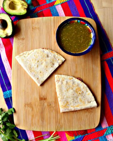 Two sincronizada wedges on a wooden cutting board next to salsa and avocado.