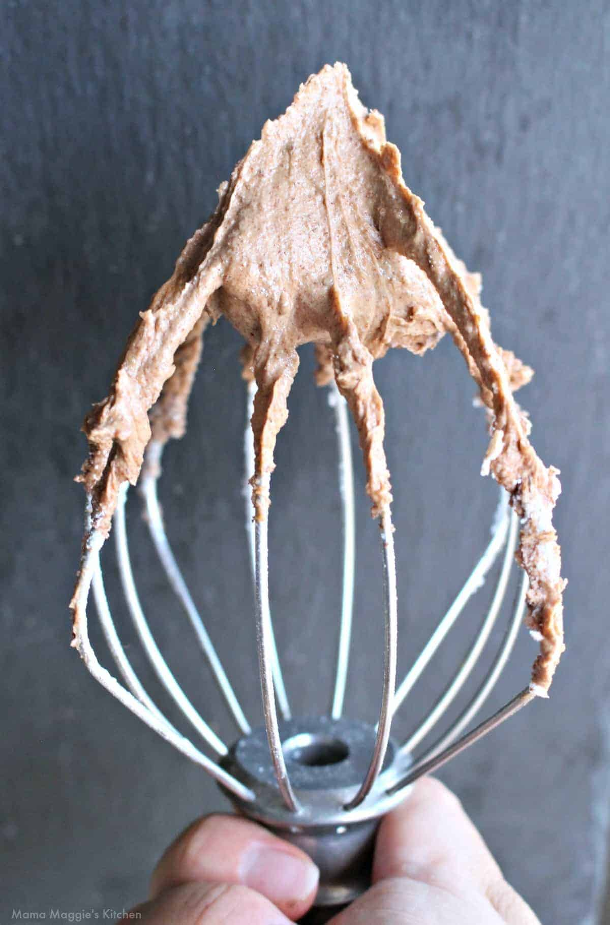 A hand holding a mixer attachment with covered with Abuelita Chocolate Frosting.