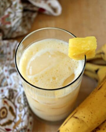 A glass of pineapple banana agua fresca decorated with a pineapple wedge and surrounded by bananas.