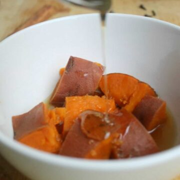 The candied syrup drizzling over the sweet potatoes in a white bowl.
