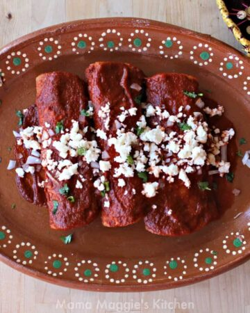 Enchiladas Rojas on a decorative Mexican plate topped with cilantro, crumbled cheese, and diced onion.
