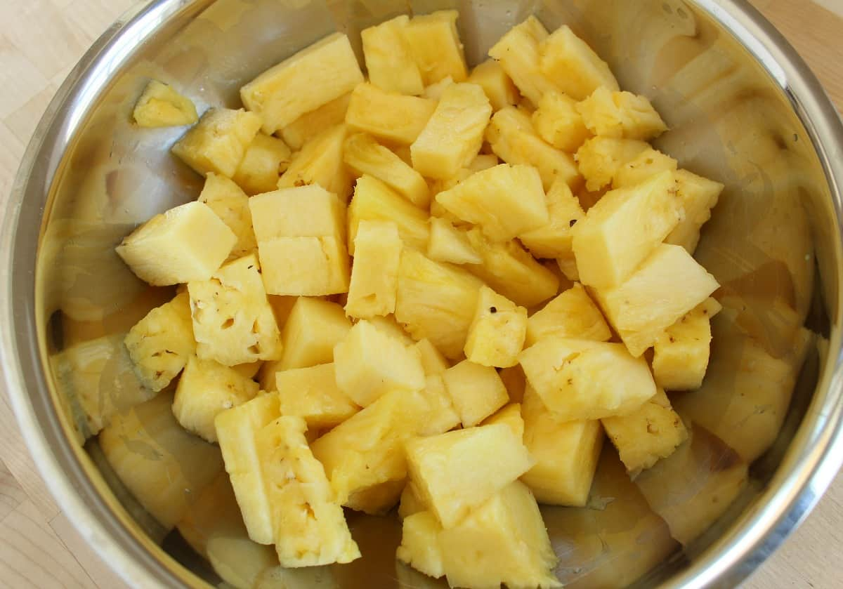 A metal bowl with freshly diced pineapple.