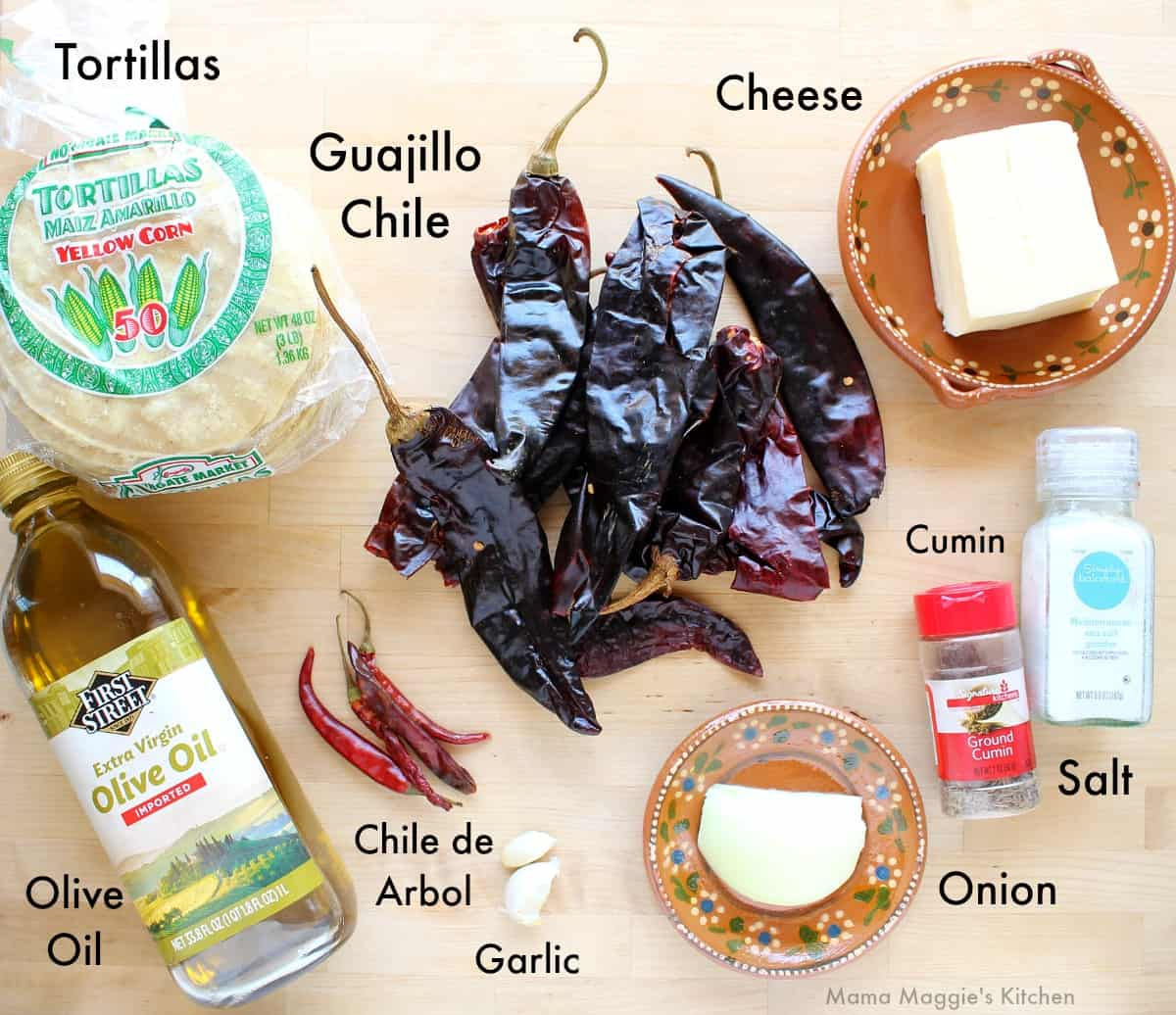 The ingredients needed to make Enchiladas Rojas labeled and on a wooden surface.