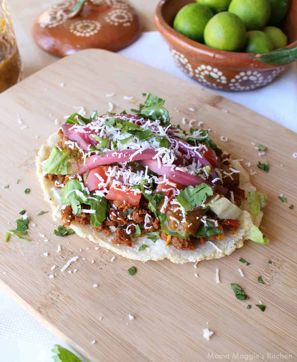 A huarache on a wooden cutting board and topped with meat, lettuce, tomatoes, and cheese.