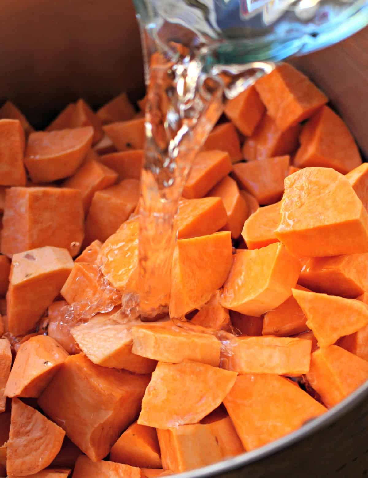 Water pouring into a pot filled with diced sweet potatoes.
