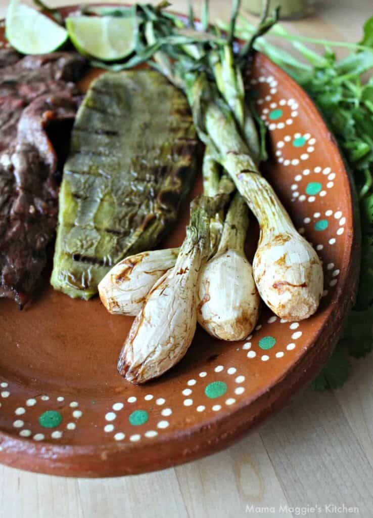 Cebollitas Asadas served on a clay plate next to grilled cactus and carne asada.