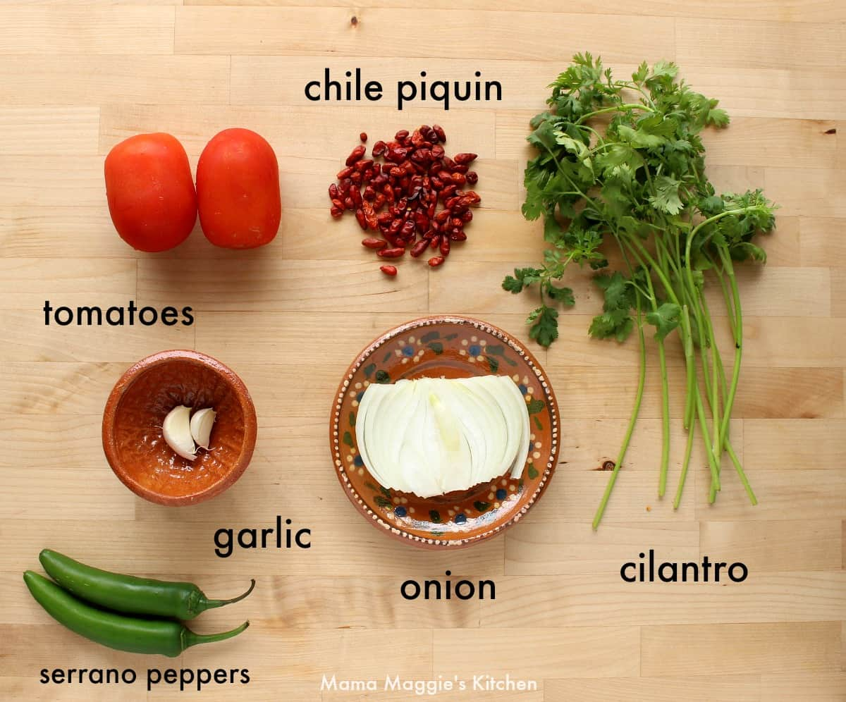 The ingredients necessary to make salsa chile piquin on a wooden surface.