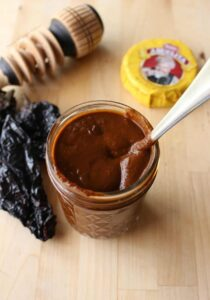 Mole sauce in a jar with a spoon inside.