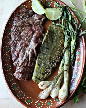 Carne asada, grilled cactus and spring onions on a decorative clay plate.