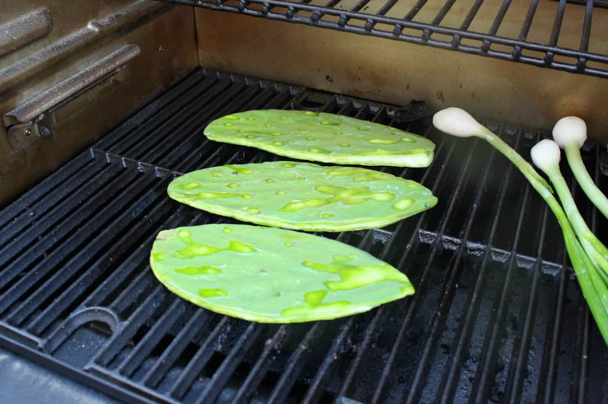Cactus paddles grilling on the grill next to spring onions.