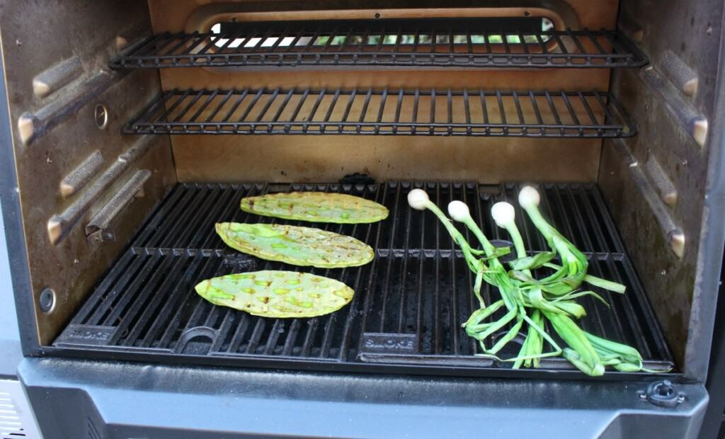 Onions and cactus paddles grilling on the grill.