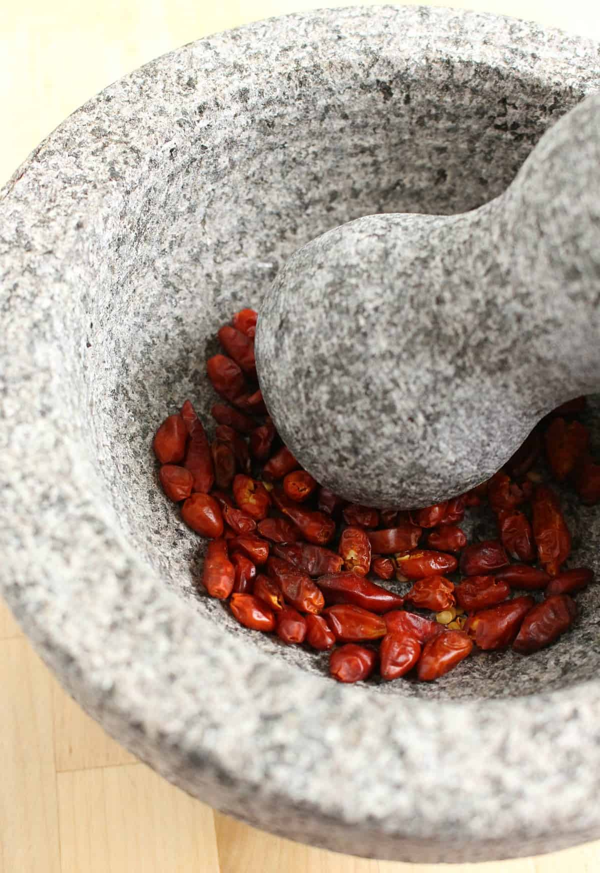 Dried chile piquin grinding in a molcajete.