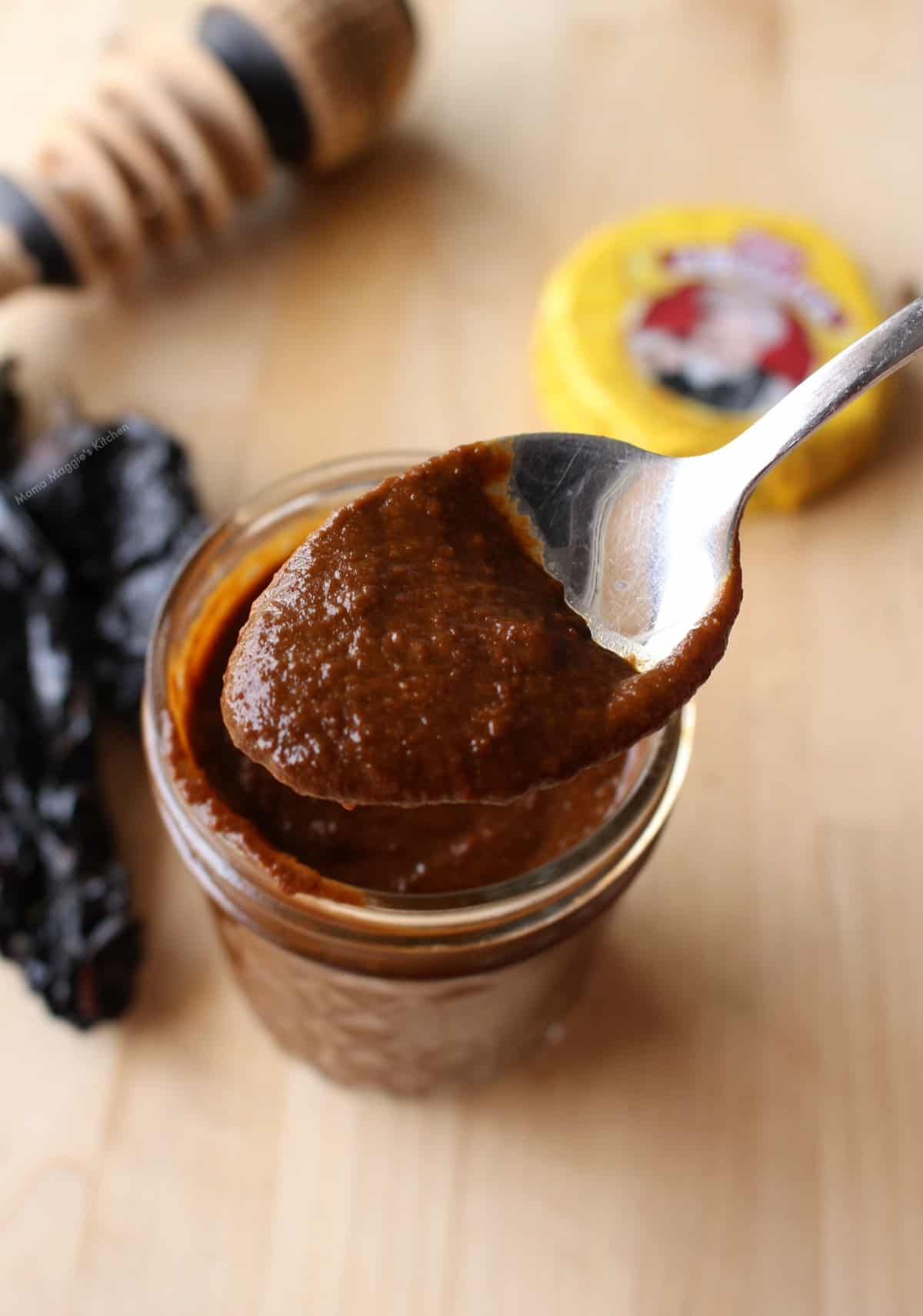 A spoon showing the mole sauce over a jar.