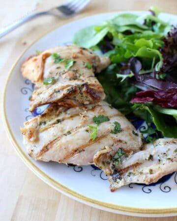 Pollo al Cilantro (Cilantro Chicken) served on a decorative plate next to a green salad.