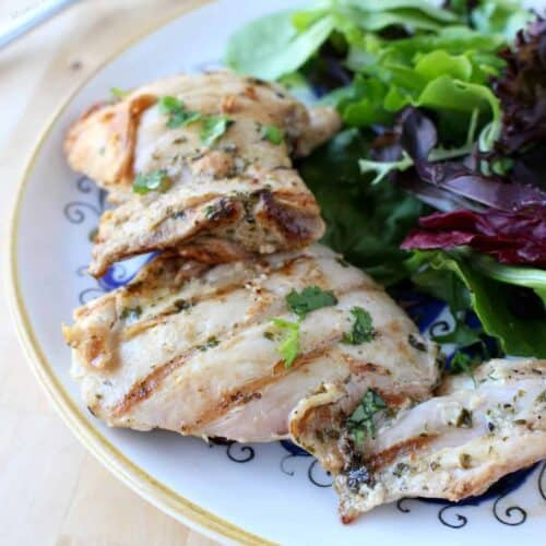 Pollo al Cilantro (Cilantro Chicken) served on a decorative plate next to a green salad.
