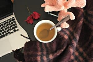 A white cup with Bougainvillea tea next to a wool scarf and a computer.