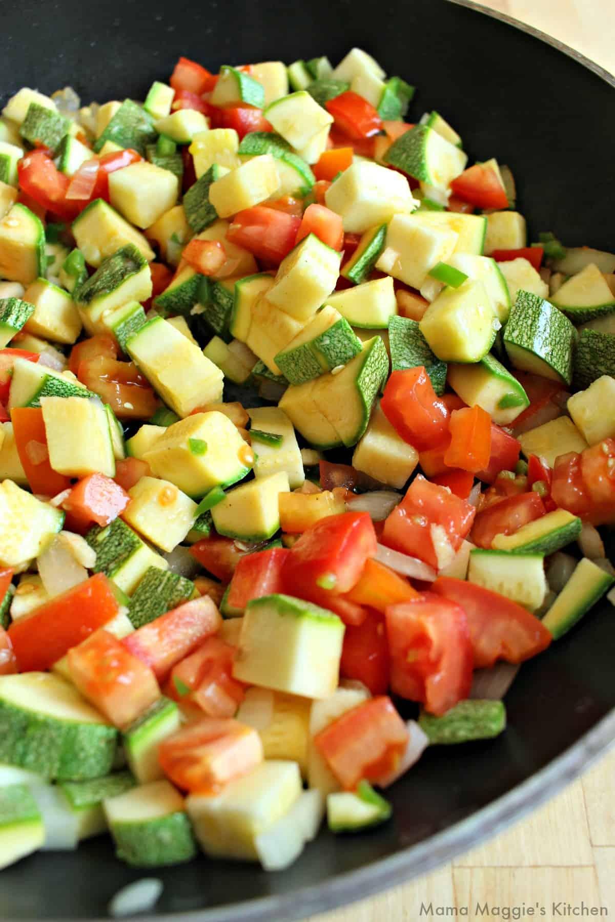Calabacitas, tomatoes, and onions cooking in a skillet.
