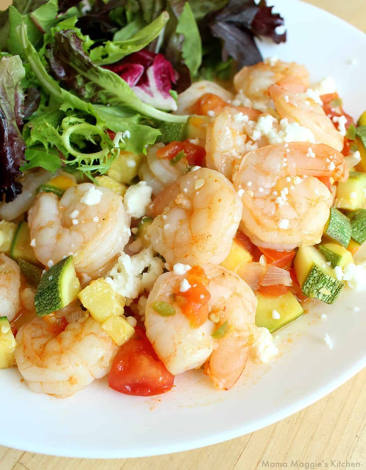 Shrimp with calabacitas served on a white plate and next to a salad.