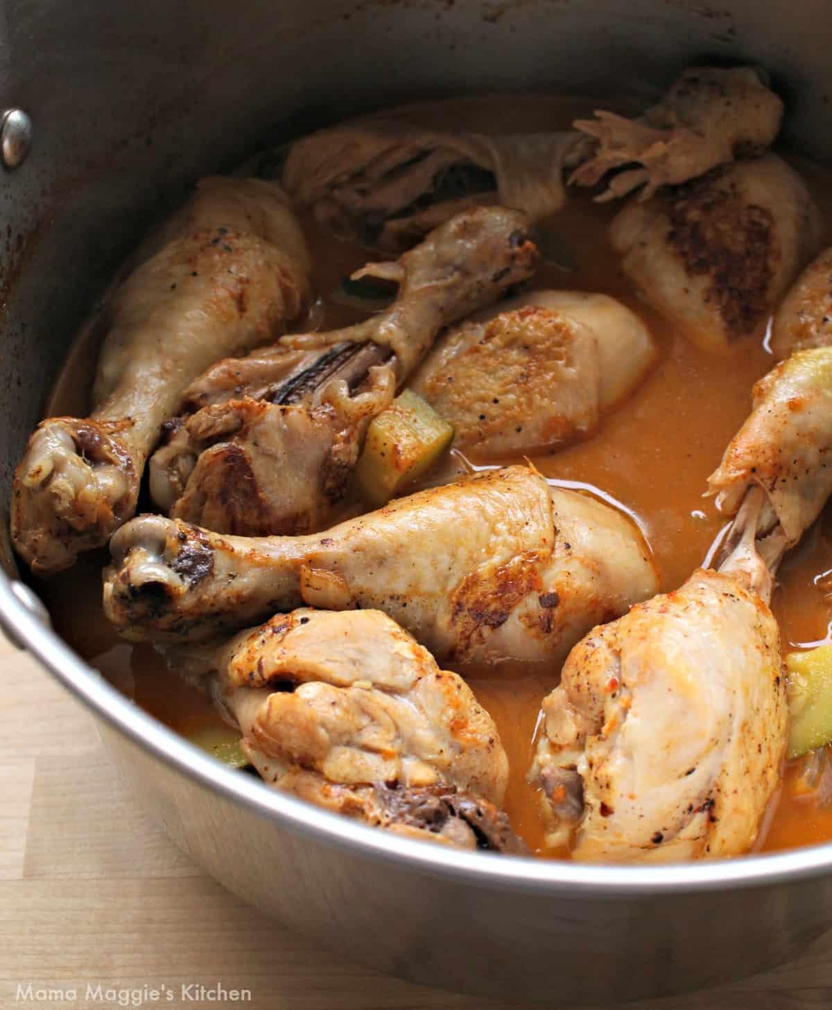 Chicken legs in a stock pot with guajillo sauce.