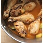 Chicken legs swimming in guajillo sauce in a stock pot.