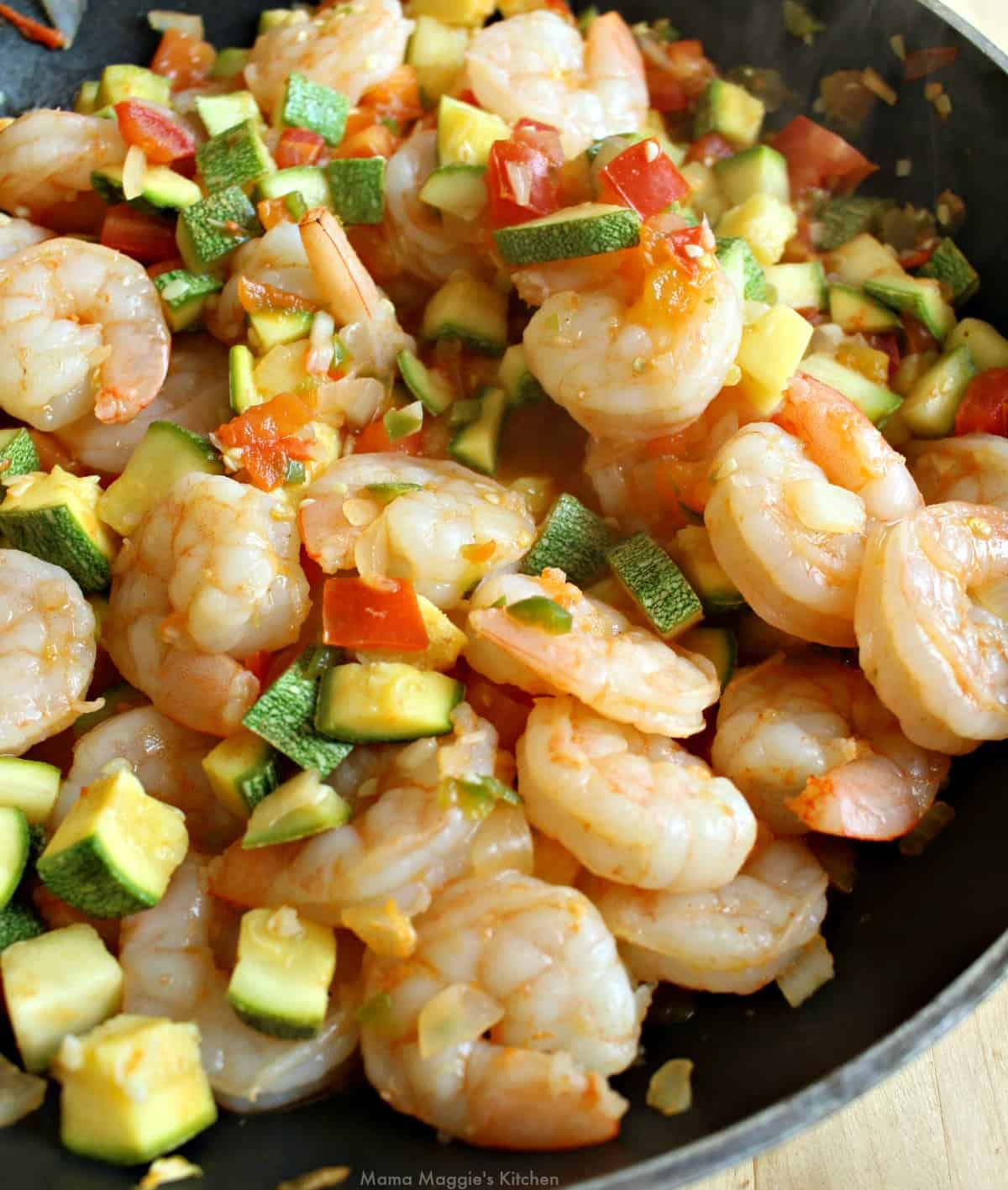 Cooked shrimp and calabacitas in a skillet.