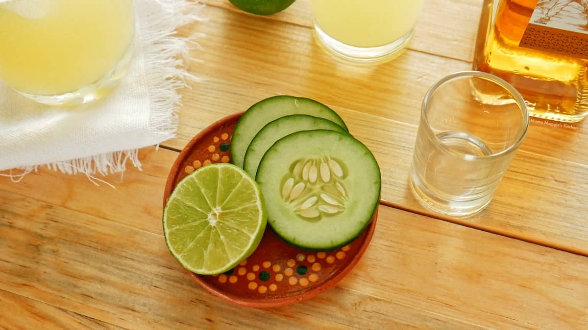 Cucumber and lime slices surrounded by glasses and tequila.