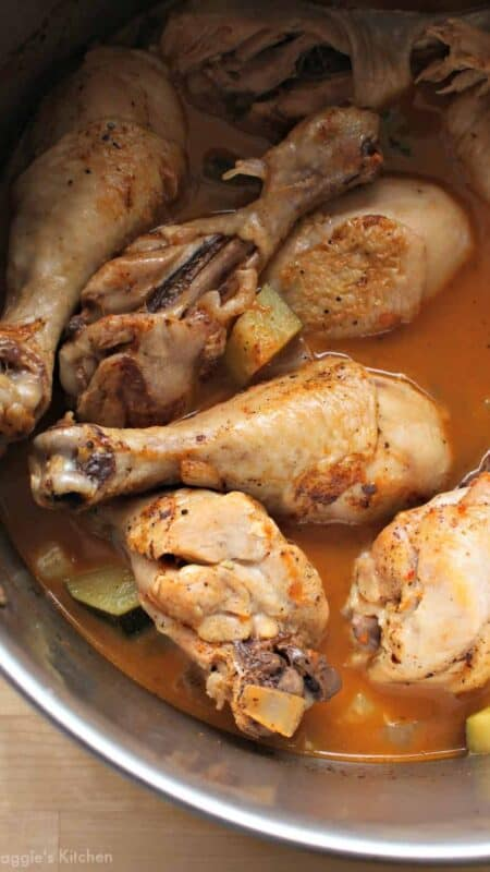 Chicken legs swimming in guajillo sauce in a stock pot.