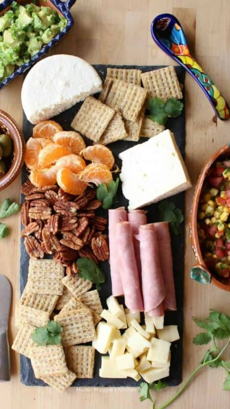 Mexican Charcuterie board with guacamole, con salsa, olives, and different kinds of Mexican cheeses.